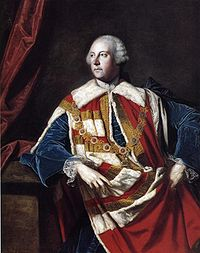 Man in his 50s wearing a white powder wig. He is wearing a decorative red and white robe over a blue jacket. He is looking to the left.