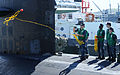 A U.S. Sailor throws a receiving line to the pier from the attack submarine USS Jacksonville (SSN 699) as the submarine arrives for maintenance in Apra Harbor, Guam, April 9, 2013 130409-N-LS794-092.jpg
