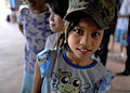 A girl at a Shepherd of the Hills Children's Foundation home in San Antonio, Philippines, wears a hat belonging to U.S. Marine Corps Master Sgt. Antoine Robinson during a community relations project March 23 130323-N-VN372-343.jpg
