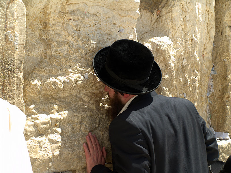 A man prays at the Western Wall in Jerusalem.jpg