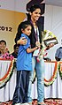 "A young sports person of ""Come & Play Scheme"" of Sports Authority of India, after presenting the cheque of Special Cash Award to Ms. Saina Nehwal, the Medal winner of London Olympics 2012, at the felicitation function.jpg"