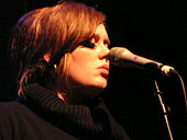 A woman wearing a black turtle neck with a microphone in front of her face