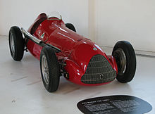 a red vintage open wheel racing car in a museum