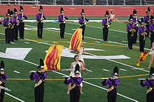 Two color guard members dressed in togas spin flags with fire designs in the middle of the DVC football field. Surrounding these color guard members are flute and saxophone players standing still and playing. They are dressed in a purple jacket and black marching pants and are wearing shakos.