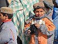 An Afghan child holds a knit hat he received from Afghan National Police (ANP) in Molla Owrang village, Nawbahar district, Zabul province, Afghanistan, Feb 120207-N-UD522-116.jpg