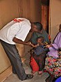 An MSF health worker examines a malnourished child.jpg