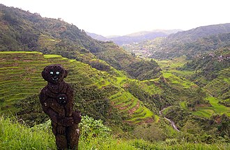 Prehistory of the Philippines - An Ifugao hogang, guardian spirits carved from tree fern trunks, overlooking the 2000-year old Banaue Rice Terraces
