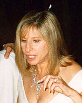 A woman with blond hair, wearing a white dress and jeweled necklace.