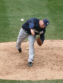 A man wearing a navy blue Brewers jersey, gray pants, and a navy blue cap shown having just thrown a ball from the pitcher's mound.
