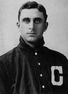 "A close-up of a man wearing a dark baseball jersey with a white ""C"" on the left chest looking into the camera."
