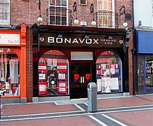 "A store called ""Bonavox Hearing Aids,"" on a brick road and next to two other businesses."