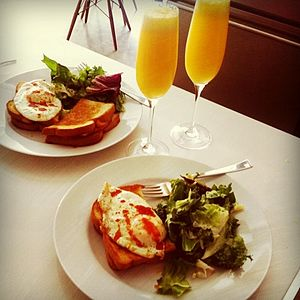 Brunch - A homemade brunch consisting of cooked eggs on toast and salad, accompanied by orange juice.