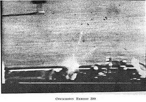 Image z313 du film de Zapruder, le tir mortel. Malgré la mauvaise qualité de la reproduction, on aperçoit la gerbe de sang vers le haut et l'avant