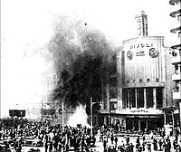 A crowd of bystanders stands outside a burning building, with black smoke coming out of the windows.