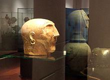 Tête stylisée en céramique avec un crâne allongé, une boucle d'oreille en or et un menton assez long, des trous et des fissures sont visibles.
