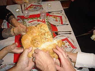 Serbian Christmas traditions - Family members break a česnica at the beginning of Christmas dinner.