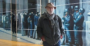 """Chas Gerretsen - Chas Gerretsen in front of one of his best known images of the 1973 """"Coup d'Etat"""", of which three are etched into a glass wall separating the  halls in the """"Museo de la Memoria y los Derechos Humanos"""" in Santiago, Chile. The walls were donated, in 2010, by the Dutch Government/Citizenry to the museum."""