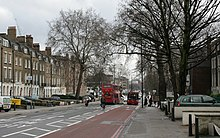 City Road as seen from Angel. A tree-lined street in winter with buses travelling in either direction.