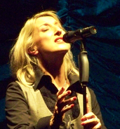 A 44-year old, blonde-haired woman, singing into a microphone with her eyes closed, facing the right of the camera.