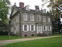 Photo shows the front and left side of a two-story stone house.