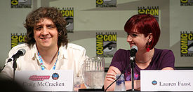 A Caucasian male wearing a white shirt sits in front of a microphone, smiling. He has large, curly brown hair which almost covers his eyes. Beside him is a Caucasian woman with short, dyed-red hair, smiling as well and looking at the man next to her.