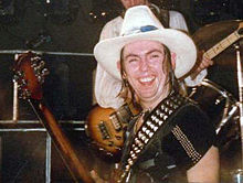A man with shoulder-length hair wears a black t-shirt and a white cowboy hat. His guitar sling sports studs.