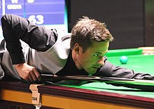 David Gilbert lining up a shot while leaning over a table