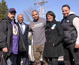 Brendon Ayanbadejo - Ayanbadejo on election day 2012 at a polling place in Baltimore with (l-r) Delegate Curt Anderson, Congressman Elijah Cummings, Mayor Stephanie Rawlings-Blake, and businessman Curtis Anderson, campaigning for marriage equality