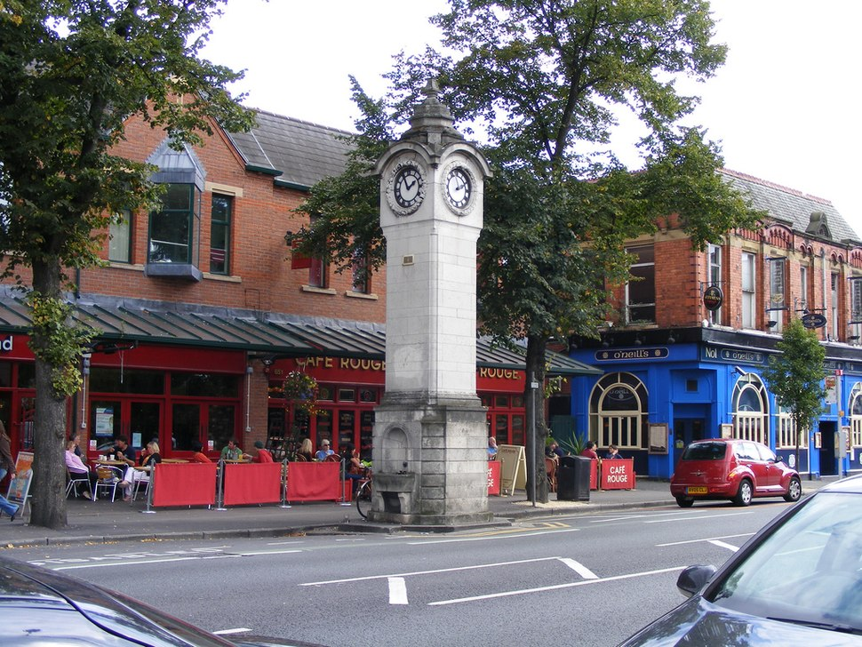 A stone tower on a street of brick buildings which include a public house and a café with tables and chairs in front of it.
