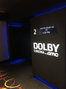 "This is a photo of the entrance to a Dolby Cinema at AMC Theatre. Rather than a typical door entrance, this theatre funnels patrons down a long, curved hallway that has scenes from the film being shown projected on the wall. This is said to help patrons become ""fully immersed"" in the movie before the feature begins."