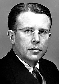 Head and shoulders of a man wearing rimless glasses, and a dark suit and tie