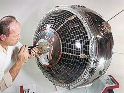 Scientist working on satellite using a tool on the presumed front of the craft