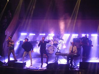 FFS (band) - FFS performing in 2015 at the Albert Hall in Manchester. From left to right: McCarthy, Russell Mael, Kapranos, Ron Mael (foreground), Thomson, Hardy (background).