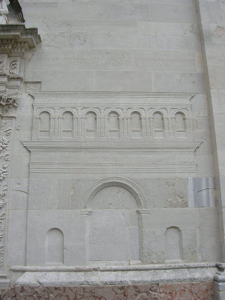 Bajorrelieve en la iglesia de San Michele, construida con las piedras caídas del Arco de Augusto. Foto de sailko