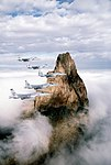 Five F-15 Eagle aircraft of the 405th Tactical Training Wing fly past a rock formation rising from the fog-covered floor of Monument Valley DF-ST-89-09403.jpg