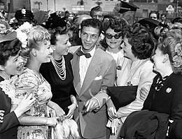 Black-and-white photograph of a young man wearing a suit and bow tie standing with several smiling ladies, with a crowd of more fans, journalists, and police officers in the background