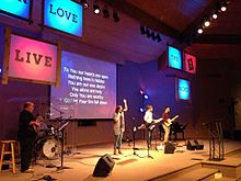A contemporary worship team leads the congregation using lyrics projected on a motion background, and coordinated lighting.