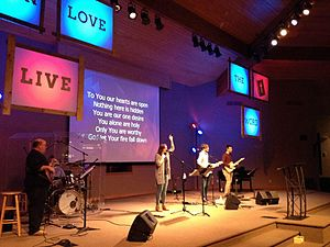 Contemporary worship - A modern worship team leads the congregation in song; projected lyrics on a motion background seen in the rear