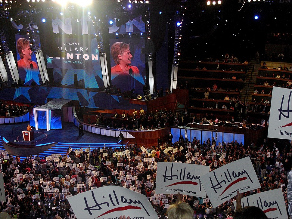 """Clinton speaking on behalf of Barack Obama before a convention audience during the second night of the 2008 Democratic National Convention in Denver. Multiple audience members in the foreground wave white flags with the word """"Hillary"""" written in marker."""