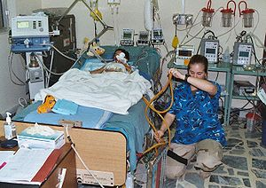 U.S. Army Nurse at the bedside of a young Iraq...