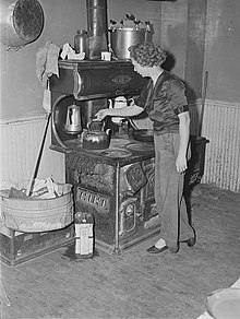 Metal can of motor oil next to wood burning stove and oven; used for getting the fire going; 1940