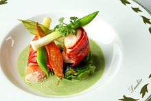 A dish with watercress, crayfish, and asparagus in a white bowl.