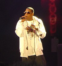 A image of an African American male wearing sunglasses with black pants and a white shirt and jacket. He is speaking into a microphone while holding it with his right hand; in the mostly dark background, a red colored wall with a design can be seen.