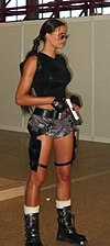 A full body picture of a dark-haired woman dressed in a black, sleeveless shirt and brown, camouflage shorts holding a silver gun.