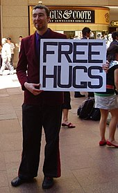 "Color photograph of a man holding a large sign saying ""FREE HUGS"" in a mall"