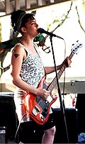 A female musician, Kathleen Hanna, singing into a microphone and playing electric bass. She is performing with the band she leads, Bikini Kill.