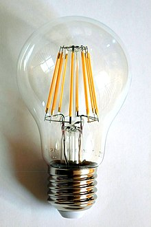 a 230 volt led filament light bulb with an e27 base the filaments are visible as the eight yellow vertical lines