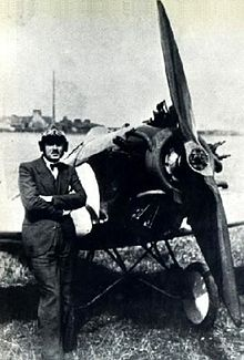 A black and white photo of a man in a suit and bow tie, wearing a pilot helmet, standing in front of a small propeller-driven monoplane