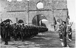 13th Demi-Brigade of Foreign Legion - The 13e DBLE towards by the Roman ruins at Lambaesis, in 1958 in an occasion revue. The Legionnaires with MAS 36, Officers and Sous-Officiers with submachine guns MAT-49. Arms packed in the holsters were probably MAC Mle 1950. Garde du Drapeau and Fanions at attention.