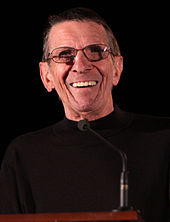 A coloured photograph of a man wearing a black jumper and glasses. He is smiling and standing on a platform.